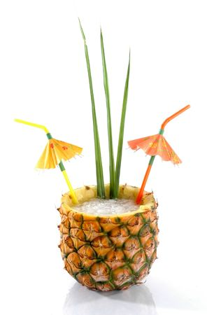 Natural Pineapple hollowed out and filled with an icy drink with tropical umbrellas and palm leaves isolated on a white background. Stock Photo