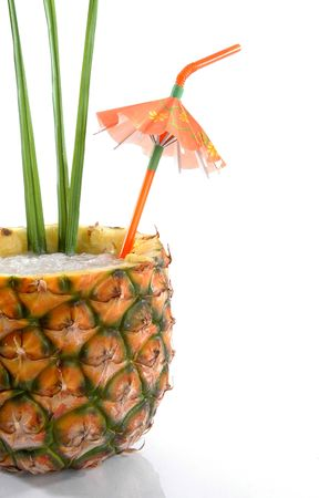 cropped out: Cropped close up, Natural Pineapple hollowed out and filled with an icy drink and a tropical umbrella.
