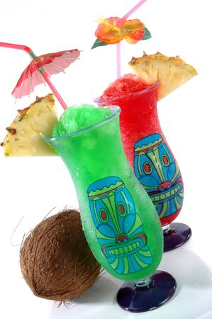 Fun plastic tiki glasses filled with colorful icy drinks and a coconut isolated on a white background.