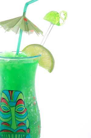 Lime tropical drink with a Flamingo swizzle and an umbrella in a tiki face plastic cup isolated on a white background, close up view. Stock Photo - 329907