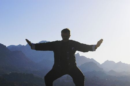 Silhouette of a man practicing Tai Chi in the morning.