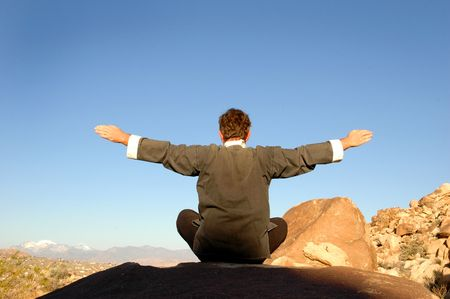 Mid aged man practicing Tai Chi meditation in the desert.