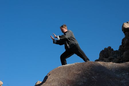 shadowed: Deeply shadowed mid aged man practicing Tai Chi on giant rocks.