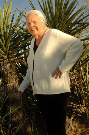 yucca: Handsome 80 year old woman posing in front of a big Yucca cactus. Stock Photo