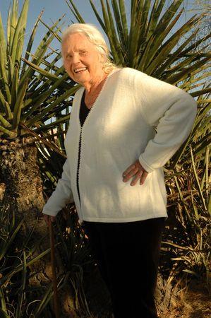 Knappe 80 jaar oude vrouw die zich voor een grote Yucca cactus. Stockfoto