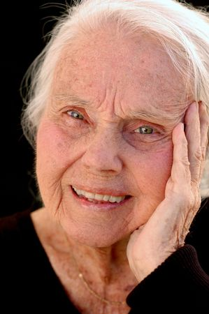 Lachend grote oma dichtbij, op zwarte achtergrond. Vrouw in haar jaren tachtig. Stockfoto