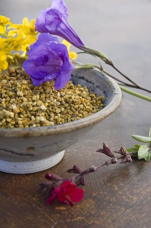 Bee Pollen in a ceramic bowl with flowers.