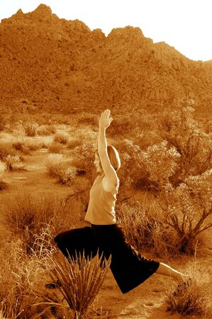 Toned black and white image of woman practicing yoga in the desert. photo