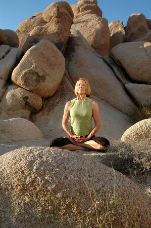 Senior woman meditating in the lotus pose outdoors in an area of large boulders.