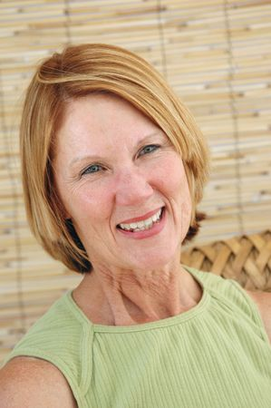 natuurlijke senior vrouw lachend in een natuurlijke interieur.