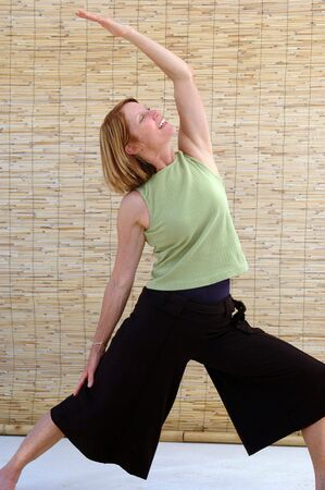 reverse: Senior woman going into the reverse warrior yoga pose.
