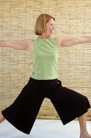virabhadrasana: Senior woman laughing as she engages in the strength building warrior pose. Virabhadrasana.