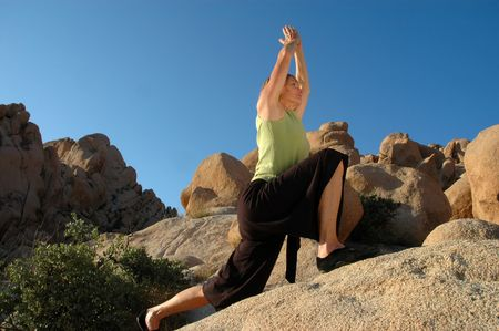 boulders: Senior woman in warrior 1 pose outdoors on large boulders.