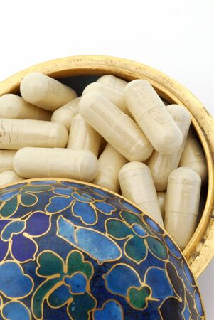 Herbal capsules in a pretty asian pill box. Stock Photo - 422543