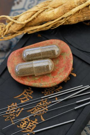 Chinese medicine. Herbal capsule, Ginseng root, and acupuncture needles. Stock Photo