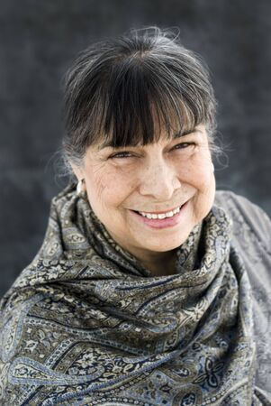 aging: Portrait of a hispanic grandmother in a grey scarf smiling.  Stock Photo