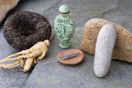 Traditional asian health items:black tea, ginseng, acupuncture needles, and medicine jar. photo