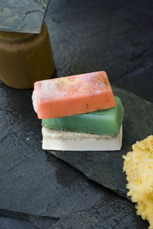 Organics soaps and sea sponge with earthen container on wet grey slate.