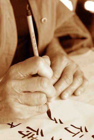 persona escribiendo: Las manos de una m�s vieja persona que escribe calligraphy chino. Fotograf�a alta del sepia del grano.