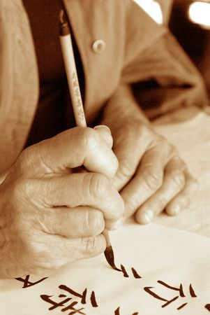 The hands of an elder person writing Chinese calligraphy. High grain sepia photograph.
