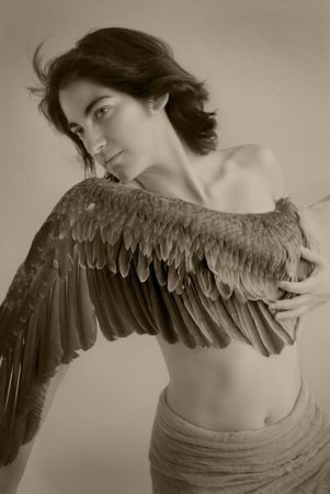 goddess of Victory. Young woman with wing across her breast. Sepia toned black and white photograph.