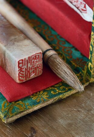 Chinese paintbrush and seal on old brocade box.  Stock Photo