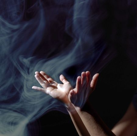consciousness: Hands lifted up to the light into an upward wave of smoke.