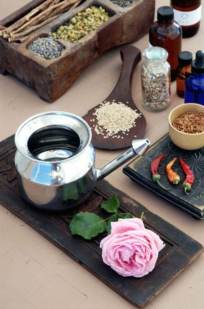 A Neti Pot and rose, chili peppers and sesame seeds, ingredients for Ayurvedic health.