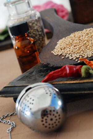 Some of the basic elements of Ayurveda: sesame, chili, tincture, tea ball, and herbs.