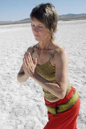 Senior Woman in yoga pose outdoors in the desert in the pranayam pose.  photo