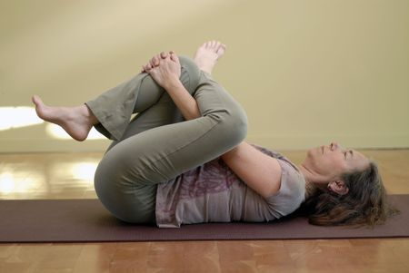 Middle aged female in a yoga pose.  photo