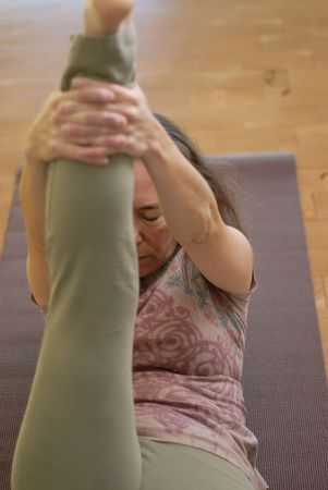 calming: Middle aged female in a gentle restorative yoga pose.