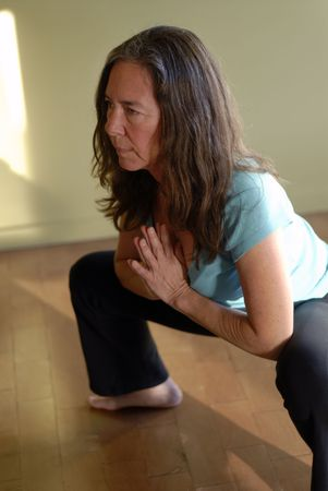 Middle aged female in a yoga pose: a deep squat with prayer hands.  photo