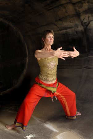 qi: Woman in Asian Yoga Qigong influenced pose in a rust cylinder. Stock Photo