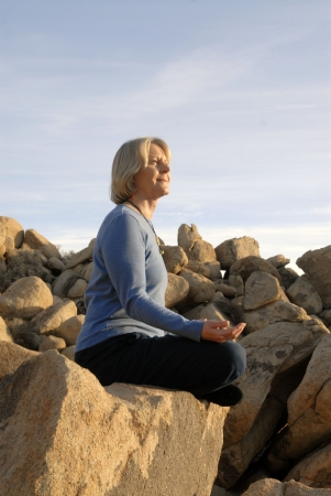 Woman in yoga meditiation pose outdoors in the boulders.