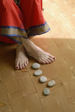 Close up of stones leading to the feet of a mature yogini. Shallow depth of focus image-critical focus on the pants trim.  photo
