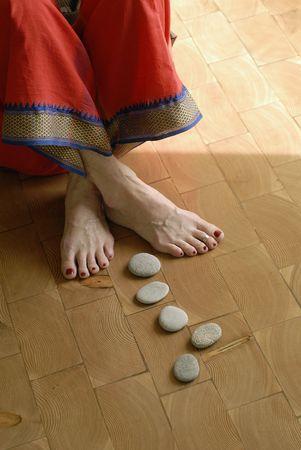 Close-up van de stenen die tot de voeten van een volwassen yogini. Ondiepe diepte van de focus op beeld kritische aandacht voor de broek trim. Stockfoto