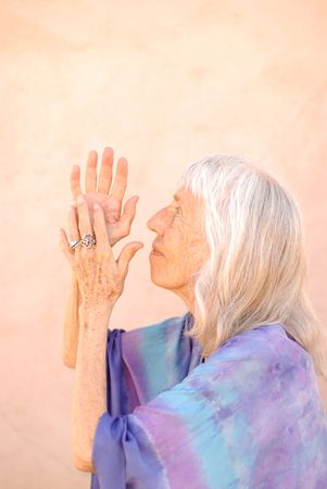 Photograph of a senior woman in devotional gesture.  photo