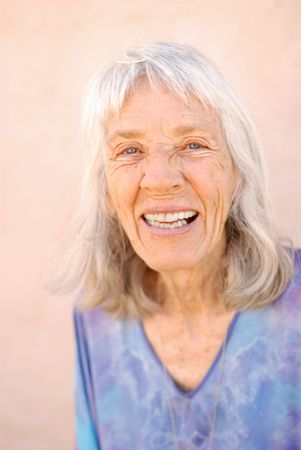 Portrait of a mature pretty woman in her late 70's laughing. photo