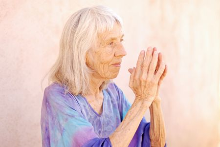 New Age senior woman holding her hands in prayer.  photo