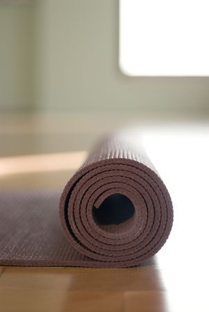 props: Simple close up of a yoga mat rolled up in a yoga studio.