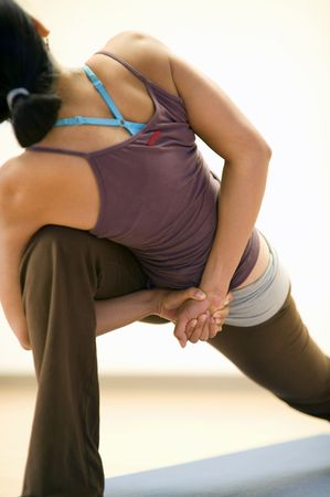 The back of a woman showing her in a bound angle yoga pose. Limited DOF-focus at the hands.  Stock Photo