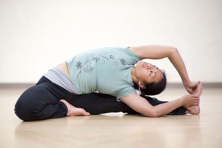 twist: Young asian woman in a seated yoga twist posture.