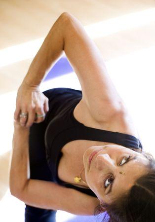 twist: Middle aged Hispanic woman doing a deep yoga twist.