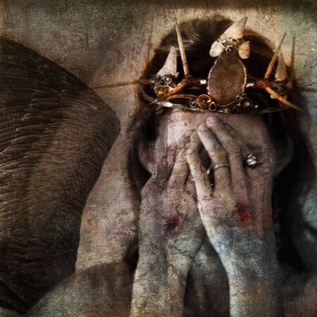 crucify: Shamanic angel martyr hiding face with stigmata on the hands. Photo base illustration. Stock Photo