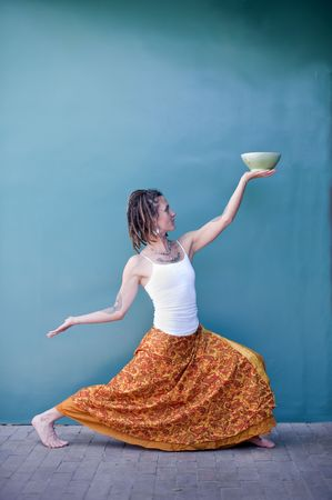 Unique woman in a dancing yoga posture offering up a beautiful ceramic bowl against the backdrop of a blue wall.