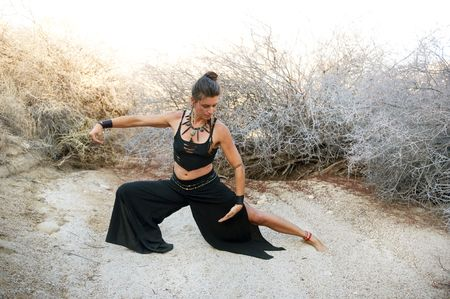 adornment: Woman with beautiful style practicing Tai chi in a natural desert environment. Art Medicine Adornment.