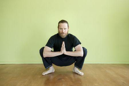 Mediados de años hombre en squat de yoga en pose de oración.  Foto de archivo - 6862780