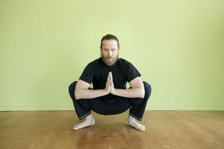 Middle aged man in yoga squat in prayer pose.