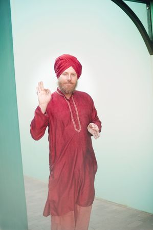 Man wearing a red turban and Indian shirt gesturing with spiritual mudras.  Stock Photo - 6862782